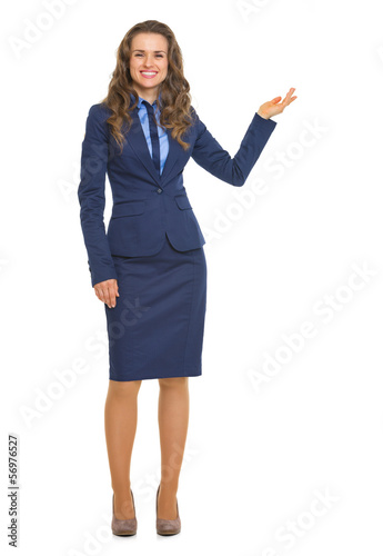 Full length portrait of smiling business woman showing something