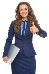 Portrait of smiling business woman with laptop showing thumbs up