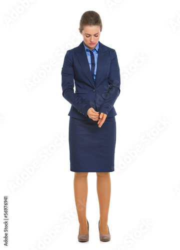 Full length portrait of thoughtful business woman adjusting cuff