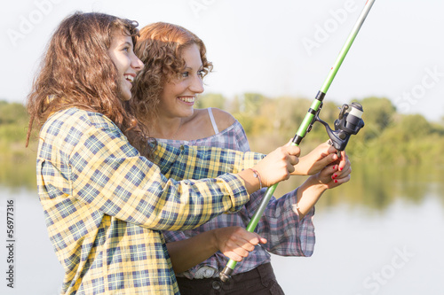 Young women fishing at river