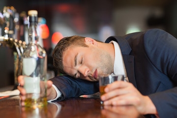 Unconscious businessman holding whiskey glass lying on a counter