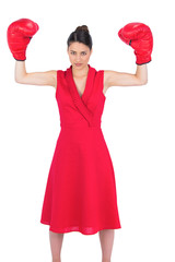 Unsmiling gorgeous brunette in red dress wearing boxing gloves
