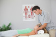 Attractive physiotherapist massaging patients neck