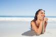 Smiling woman lying down on beach