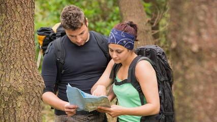 Fit couple reading map in a forest