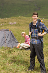 Happy man carrying backpack while girlfriend is pitching tent