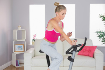 Sporty focused blonde training on exercise bike listening to mus