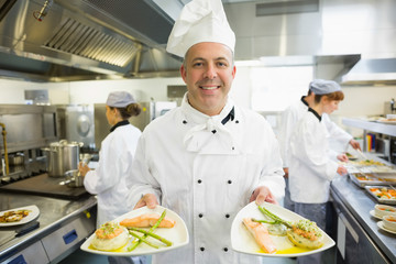 Mature head chef presenting proudly some dinner plates