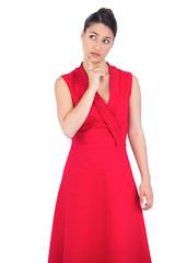 Thoughtful elegant brunette in red dress posing