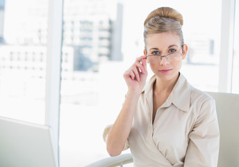Serious young blonde businesswoman looking over her glasses