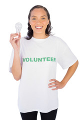 Thoughtful volunteer woman holding a light bulb