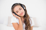Peaceful smiling brunette listening to music with closed eyes