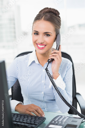 Smiling brunette businesswoman phoning