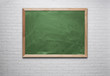 Blank green chalkboard on the brick wall