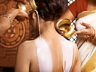 Woman having Ayurvedic milk  spa treatment.