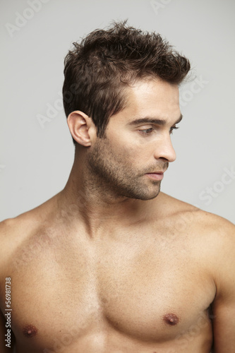 Shirtless mid adult man looking away, studio