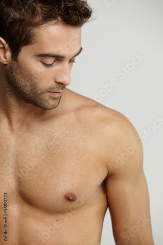 Shirtless mid adult man looking down, studio