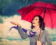 Smiling Woman with Umbrella over Autumn Rain Background