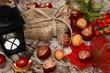 Herbstdekoration mit Windlicht, Kastanien und Hagebutten