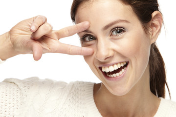 Portrait of a woman making the peace sign on a white background