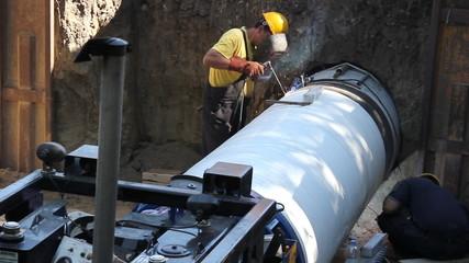 Welders weld large pipe in a hole, teamwork