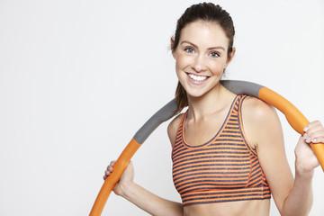 Young active woman using a hula hoop