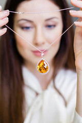 Girl holding necklace with yellow sapphire at jeweler's shop