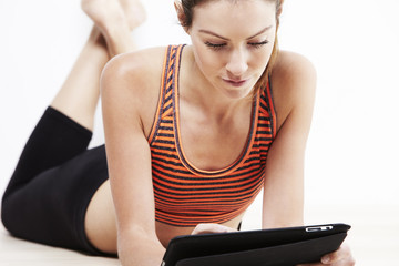 Young attractive woman using a digital tablet after workout