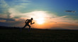 Silhouette man running on meadow, sunrise