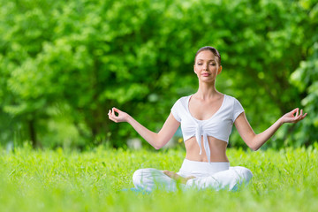 Woman with closed eyes sits in lotus position zen gesturing