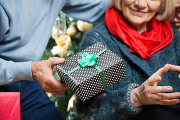 Man Giving Christmas Present To Woman At Store