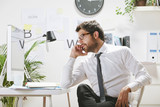 Young businessman talking on smartphone in office,