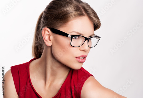 Young stylish girl in optical glasses posing in studio.