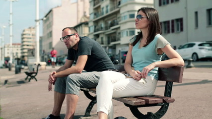 Conflicted young couple sitting on bench in the city