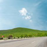 asphalt road to horizon in mountain under light clouds