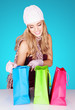 Delighted woman peeking into her shopping bags