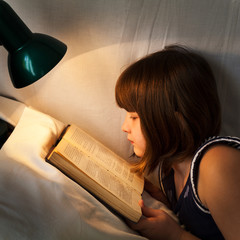girl reading book on bed at night