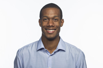Young black man smiling against white background