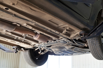 car lifted on auto hoist at service station