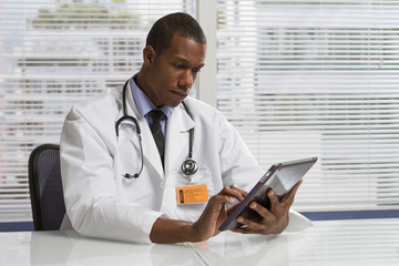 African American doctor holding electronic tablet, horizontal