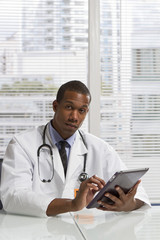 African American doctor holding electronic tablet, vertical