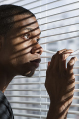 Young nervous black man looking out window, vertical