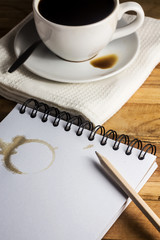 paper, pencil and white cup of coffee on desk