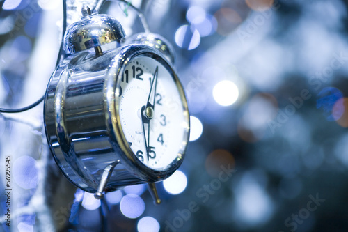 metal clock on a holiday background with sparkles and highlights