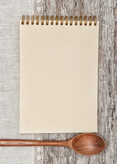 Paper notebook, wooden spoon and linen fabric on the old wood