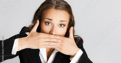 Business woman covering mouth, over gray