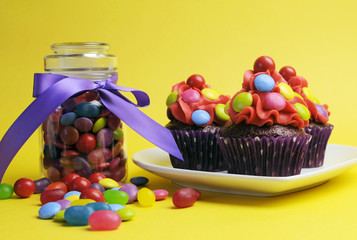 Bright colored candy cupcakes with candy jar on yellow.