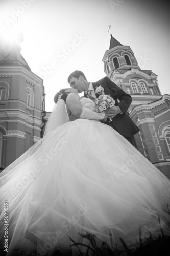 married couple kissing against church rooftops