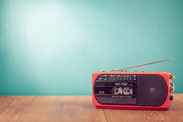 Retro red radio cassette player in front mint green background
