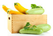 Raw yellow and green zucchini in wooden crate, isolated on